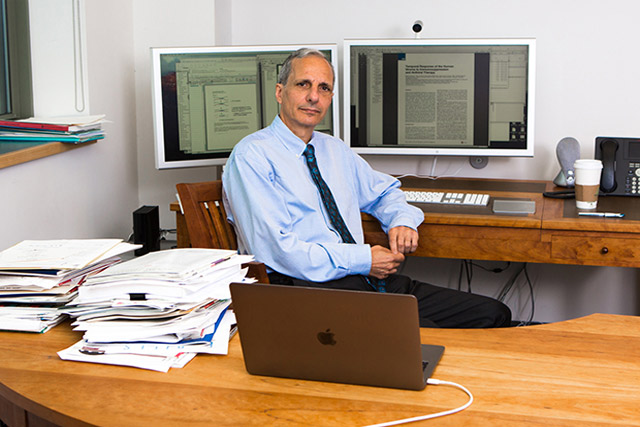 Doctor-Robert-Darnell-sits-behind-his-desk-at-the-New-York-Genome-Center